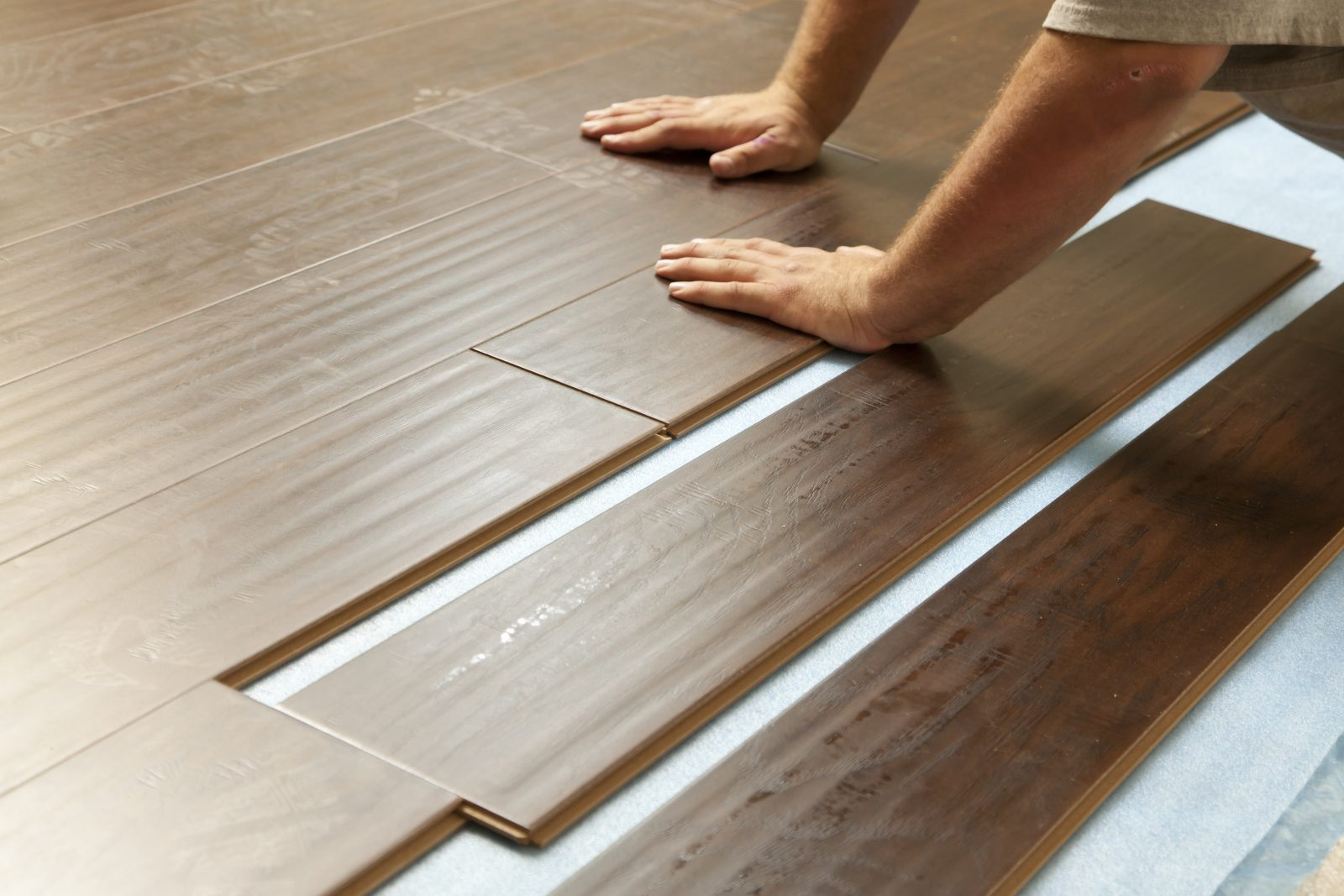 Man Installing New Laminate Wood Flooring | The Carpet Stop