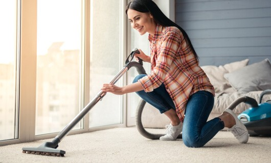Lady vaccuming carpet | The Carpet Stop